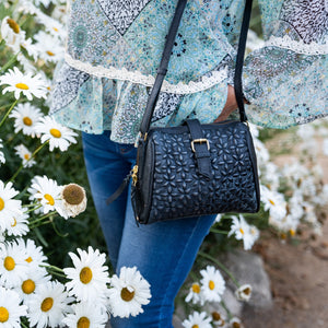 Woman standing in a field daisies, Sam Quilted Crossbody Bag.