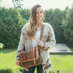 Woman outside wearing a green messenger bag with a woven leather flap, Abby Woven Messenger Bag.