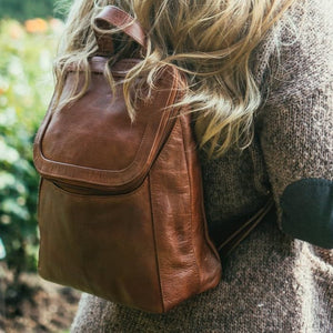 Small brown leather backpack on a woman at a flower garden, Addie Leather backpack.