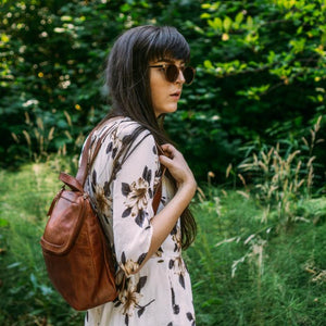 backpack on model outdoors with lush background, retro sunglasses, Addie Leather Backpack.