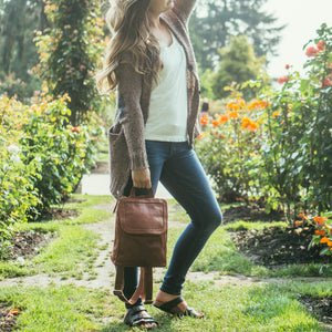 front view of Brown Backpack, backpack on model outdoors, flowers in the background, Addie Leather Backpack.