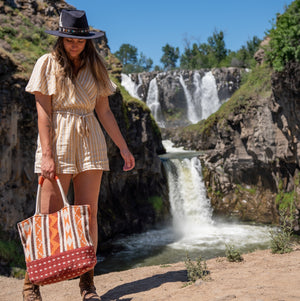 Woman in front of a waterfall holding a fabric tote, Cara Fabric Tote.