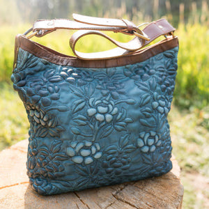 Denim blue leather shoulder bag on a wood stump outside, Cari Quilted Shoulder Bag.