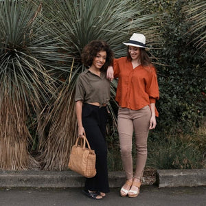models outdoors holding a honey colored tote with woven leather, Freya Crossbody Bag.