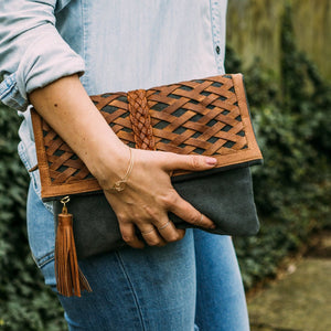 Close up of a woman's hand holding gray suede clutch, Ivy Clutch.