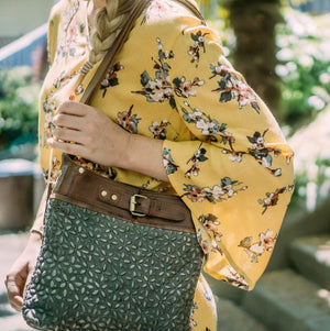 Woman wearing small leather bag outside with yellow floral top, Joan Quilted Crossbody Bag.