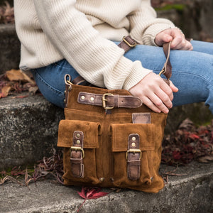 Woman sitting on concrete steps, next to her is the Joan Suede Crossbody Bag in tobacco.