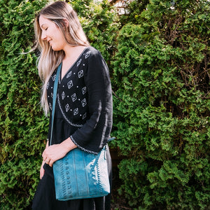 Woman wearing blue crossbody bag, June Crossbody Bag.
