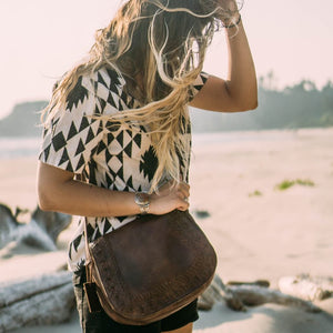 Woman in shorts on the beach carrying brown leather crossbody bag, Saddle Crossbody Bag.