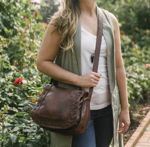 Woman in the Portland Oregon Rose Garden, carrying brown leather crossbody bag, Saddle Crossbody Bag.