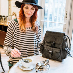 woman drinking tea with a leather backpack on the table, Sadie Leather Backpack,.