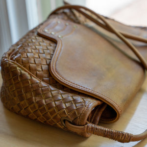Woven brown leather bag on a desk, Sawyer Woven Shoulder Bag.