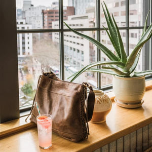 leather purse on window in an office, Side Tie Shoulder Bag.