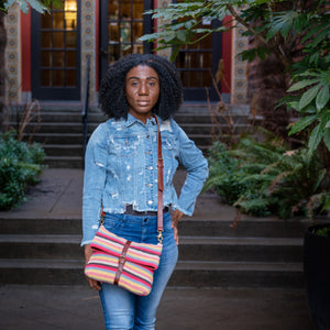 Woman standing in front of an apartment wearing a colorful striped cotton knit bag, Yolanda Cotton Foldover Crossbody Bag.