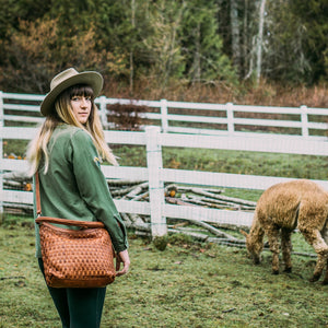 Skylar Woven Leather Bag, woven leather, women on a farm wearing a brown woven leather crossbody bag.