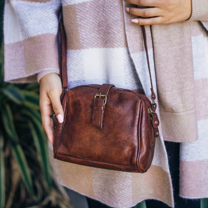 Close up image of a small  brown leather bag being worn by a woman, Sam Leather Crossbody Bag.