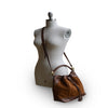 Mannequin wearing brown suede bucket bag, Rowan Suede Crossbody Bag.