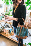 Woman standing in a plant shop wearing a teal suede crossbody bag, Rowan Suede Crossbody Bag.