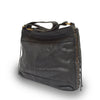 Black leather shoulder bag at an angle and strap down, Side Tie Shoulder Bag.