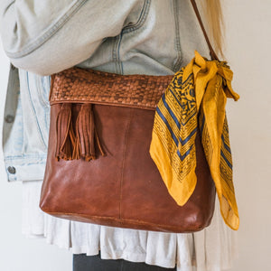 Brown leather shoulder bag on a woman's shoulder, Nomi Shoulder Bag.