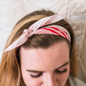 Red scarf tied around a woman's hair like a headband, Sweet Spring Bandana.