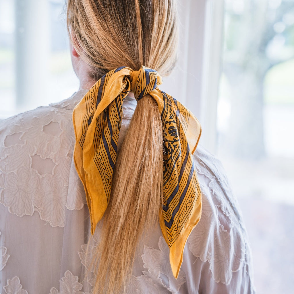Woman with yellow scarf tied around her blonde hair, Sweet Spring Bandana.