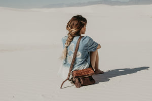 Woman sitting on the sand with a woven brown bag, Iris Leather Clutch.