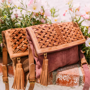 Ivy Clutch outside by flowers pink, purple and pecan, light brown suede, leather, purse, removable strap.