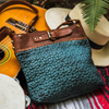 Blue leather crossbody bag on a blanket with musical instruments and a hat, Joan Quilted Crossbody Bag.