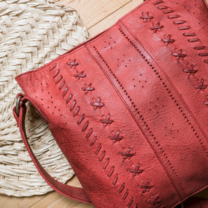red purse on the floor with straw fan, June Crossbody Bag.