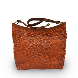 front view of Rust leather shoulder bag with handle up, quilted floral detail, quilted Cari Quilted Shoulder Bag.