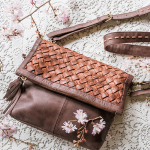 leather purse on carpet with spring flowers, brown bag, pink flowers, iris clutch.