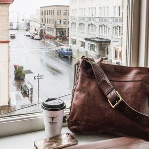 cognac brown purse by coffee and cell phone in front of window of hotel in Astoria, Oregon, dark brown handbag on window sill, Side Tie Shoulder Bag.
