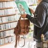 woman in music store holding backpack, mini backpack, brown bag, Sadie Leather Backpack.