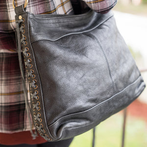black leather handbag on a person wearing a flannel shirt on porch, Side Tie Shoulder Bag.