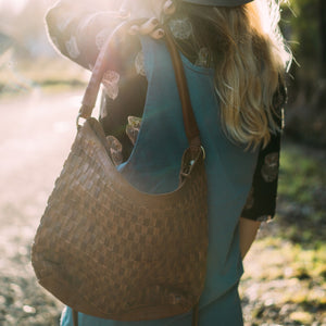 woman wearing leather handbag at sunset, Skylar Woven Leather Bag.