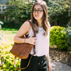 Skylar, woven leather, woman outdoors wearing brown woven leather bag, glasses, bushes, sunny.