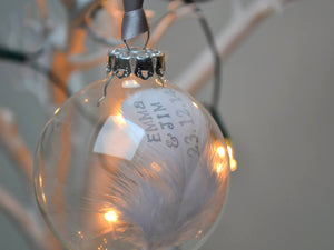 Hand stamped feather in a glass bauble