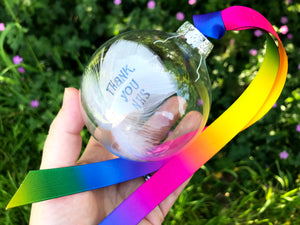 Hand stamped double feather in a glass bauble, with blue text and rainbow ribbon