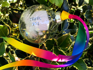 Hand stamped feather in a glass bauble, with blue text and rainbow ribbon