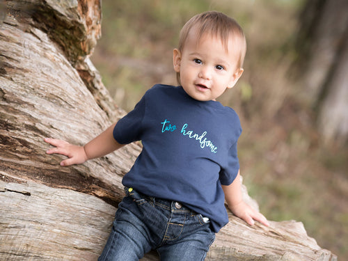 Two Handsome navy t-shirt by Little Foxglove modelled on a toddler, sat outside on a tree