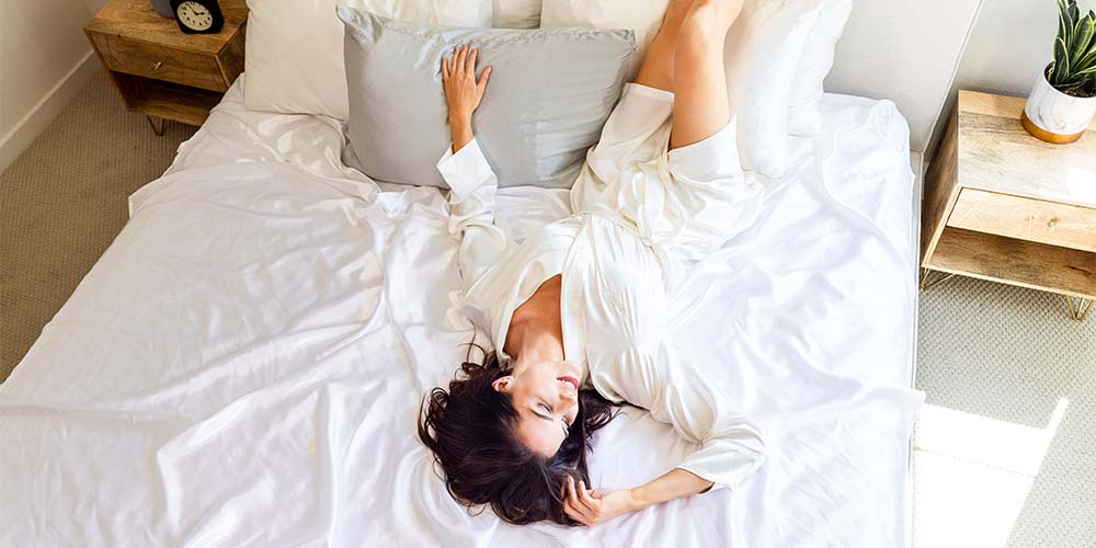 woman lying down on the bed wearing Blissy white mulberry silk robe