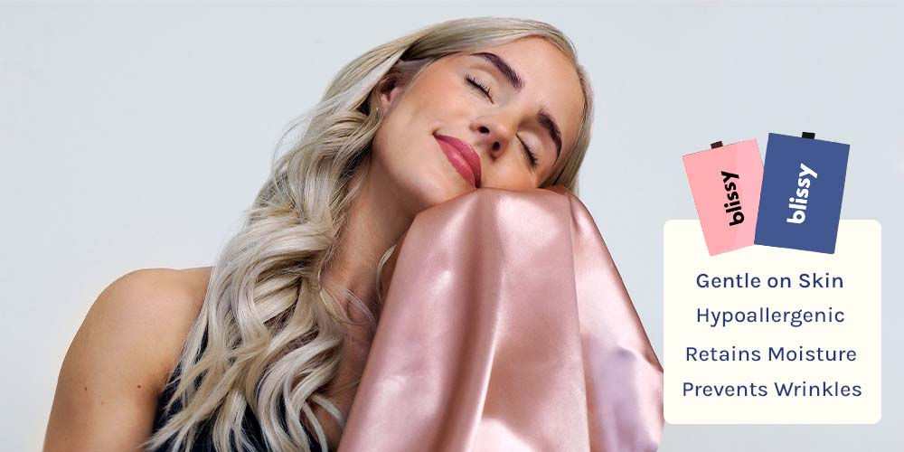 woman feeling the smoothness of a blissy rose gold silk pillowcase on her face ft. skin benefits