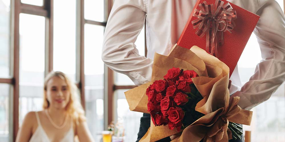 couple on a romantic dinner with boyfriend holding roses and gifts