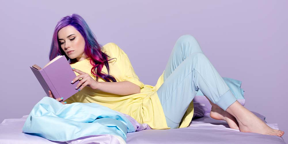 woman with colorful hair reading a book on a bed