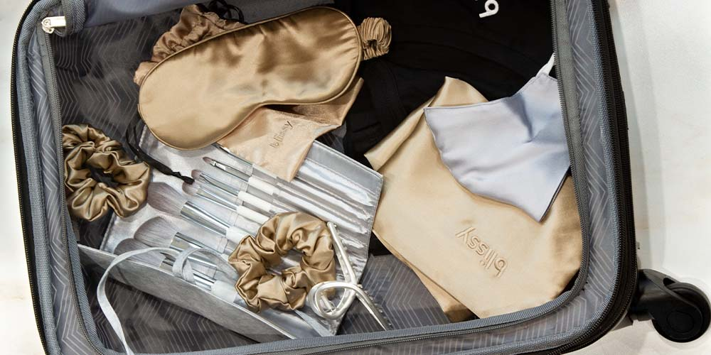 Travel luggage top view with Blissy silk sleep essentials in taupe and silver makeup brush