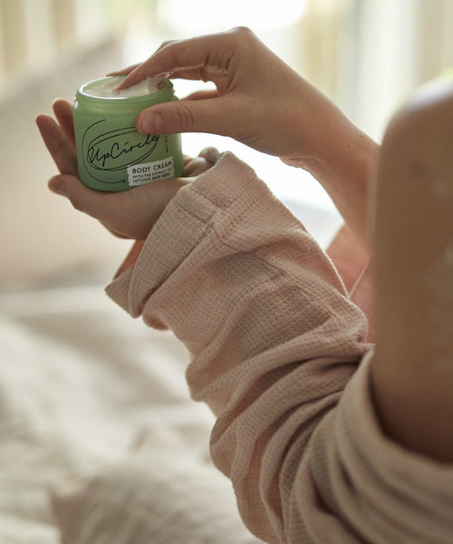 Woman holding open UpCircle body cream jar showing creamy texture