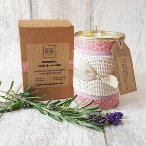 Upcycled English rose candle hand decorated with pink design next to outer cardboard box