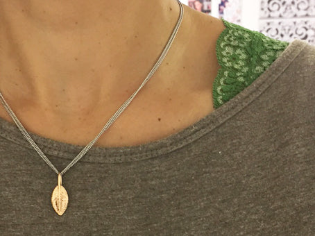 Yellow gold feather of friendship pendant charm styled on a sterling silver chain