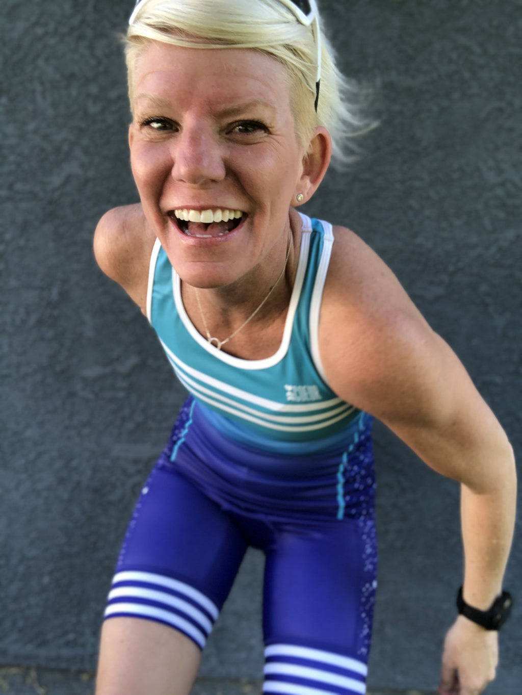 Lifestyle image of woman wearing a blue triathlon tank top